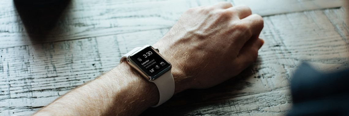 Man's arm on a table with a smart watch