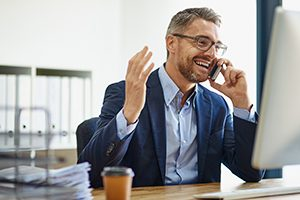 Man on the phone at his desk smiling