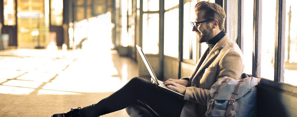 Homme dans un couloir ensoleillé qui regarde son portable
